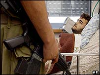 Israeli soldier guards wounded Hamas suspect after raid in Gaza