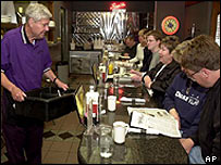 Democratic presidential candidate Bob Graham carries a tub full of dishes at a diner in Des Moines, Iowa, 11 May 2003