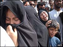 Women weep as they search for relatives at grave site