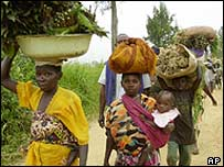 Congolese people pass through Dele checkpoint five kilometres from Bunia, as they return to their homes carrying their belongings to Bunia, 28 June 2003