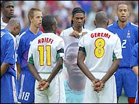 Cameroon captain Rigobert Song (centre) stands with a picture of Marc-Vivien Foe as the players observe a minute's silence before the Confederations Cup final