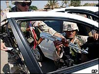 US Army troopers check the papers of an AK-47 assault rifle which was found during a search at a checkpoint, Fallujah, 29 June 2003
