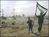A Palestinian security officer places a national flag near Gaza's main highway