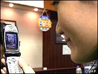 NTT DoCoMos employees demonstrate the 3G cell phone