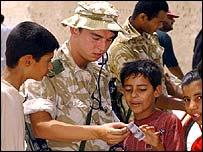 Iraqi children talk to a British soldier in Umm Qasr