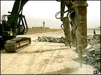 Engineers work around a bomb crater on the tarmac of Baghdad International Airport