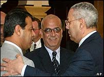 Saeb Erakat watches as US Secretary of State Colin Powell shakes hands with Mohamed Dahlan