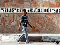 A girl walks past a sign in the town of Jericho on the eve of Colin Powell's visit
