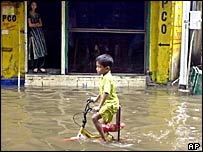 A boy pedals a bicycle through the flooded street after heavy monsoon rains in India