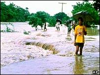 Bangladeshi villagers wade through floods at Fatikchhari district southeast of Dhaka