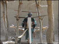 An old man in Konseguila, southern Mali, weaves cotton on a traditional loom