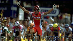 Mario Cipollini raises his hands in triumph as he crosses the line first