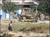 A Palestinian boy throws stones at an Israeli army bulldozer