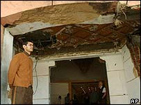 A doorman in the damaged entrance to the Safir Hotel