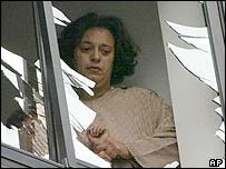 A woman looks through a smashed window at the Jewish centre