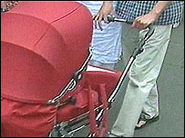 Couple push 1970s retro-style pram down street