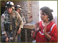 A woman stands by as US soldiers make raids on Baghdad homes
