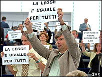 Green Party members show placards reading everyone is equal before the law before Berlusconi reads his speech