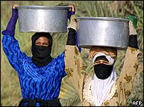 Iraqi women carry basins of water on their heads on the outskirts of Najaf, 2 July 2003