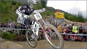 A downhill mountain biker flies through the air