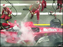 The Ferrari mechanics put out the pit fire on Michael Schumacher's car during the Austrian Grand Prix
