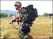 Indonesian airborne soldier moves to his meeting point after parachuting into an area near the airport in Banda Aceh