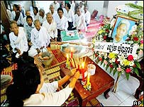 Cambodian women light candles and incense during prayers for Khieu Ponnary