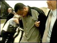 Sam Onogigovie being led away from court