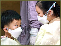 A young boy checks his sister's mask as his whole family is admitted to hospital with Sars-like symptoms, Taipei.