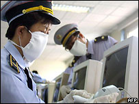Chinese health officials disinfect a computer