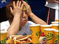 Takeru Kobayashi from Nagano, Japan, recovers at the end of the hot dog eating competition, 4 July 2003