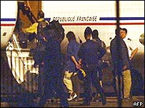 van Colonna is escorted by special police after his capture in 2003