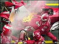 Ferrari mechanics extinguish the flames licking Michael Schumacher's car