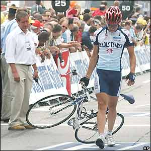 Gerolsteiner's Olaf Pollack picks up his bike and walks away after a mass crash
