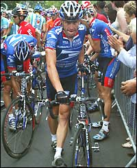 Lance Armstrong retrieves his bike after being brought down in the mass crash