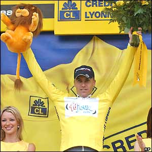 Brad McGee stands on the podium wearing the yellow jersey