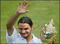 Roger Federer shows off the Wimbledon trophy