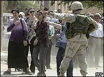 US soldier directs students as they evacuate the campus of Baghdad University following the shooting of a US soldier,  6 July 2003