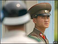 A North Korean soldier (R) looks at a South Korean soldier