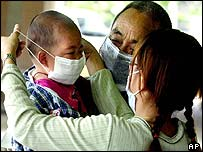 A mother puts a protective surgical mask on her son's face in Taiwan's southern port city of Kaoshiung