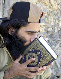 Shah Mohammad kisses the Koran