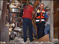 Israeli medics and police examine wreckage of house