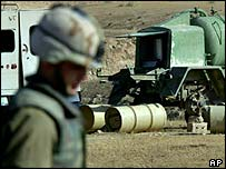 A US soldier looks at suspicious drums of liquid in Iraq