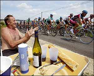 A supporter eating by the side of the road cheers on the cyclists during the third stage