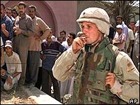 US soldier smokes a cigarette while guarding line of Iraqis at money exchange office in Baghdad
