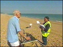 A Shepway Council worker hands out warning leaflets on the beach