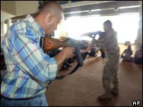 Iraqi recruit is taught how to handle a rifle by a US soldier