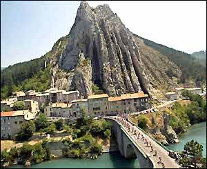 The peloton cross the River Durance at Sisteron in front of the Rocher de la Beaume