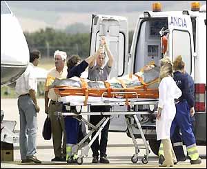 Joseba Beloki is loaded into an ambulance after arriving in Spain