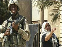 US soldier stands guard by local woman in Iraq